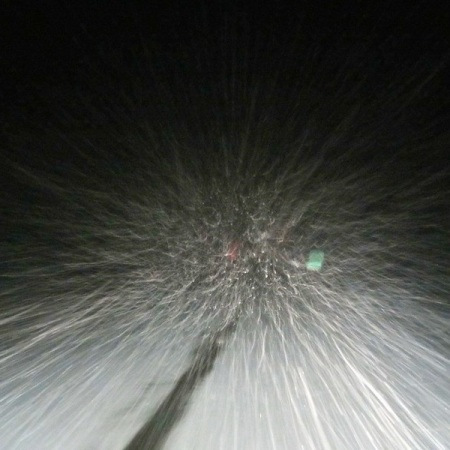 View of a snowstorm through a car's windshield at night.