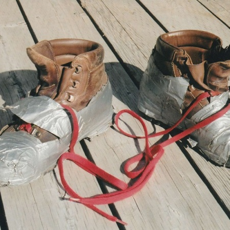 Disintegrating leather hiking boots covered in duct tape.