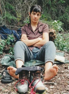 Ulrike sits on the ground with blister-covered feet and disintegrating hiking boots.