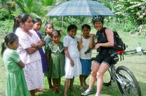 A Temple-to-Temple participating racer smiles next to a group of Mayan girls in a jungle clearing in Lubaantuun, Belize.