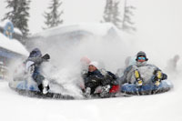A family kicks up the snow on snow sleds in British Columbia, Canada