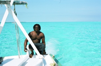 A man steers a fishing boat on tropical water near Caye Caulker, Belize.