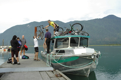 A group of cyclists unload bikes from a boat on Pitt Lake, BC.