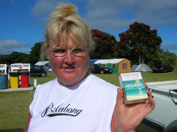 "A sun-tanned woman holds up a package of ""Holiday"" cigarettes in a campground in Raglan, New Zealand."