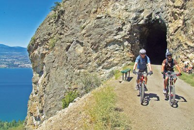 Two cyclists emerge from a rail-trail tunnel on the Kettle Valley Train near Penticton, Canada.