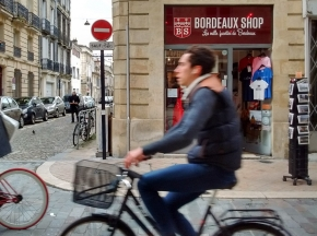 A man rides a bicycle past a tourist shop in Bordeaux, France.