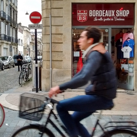 A man rides a bicycle past a tourist shop in Bordeaux, France.