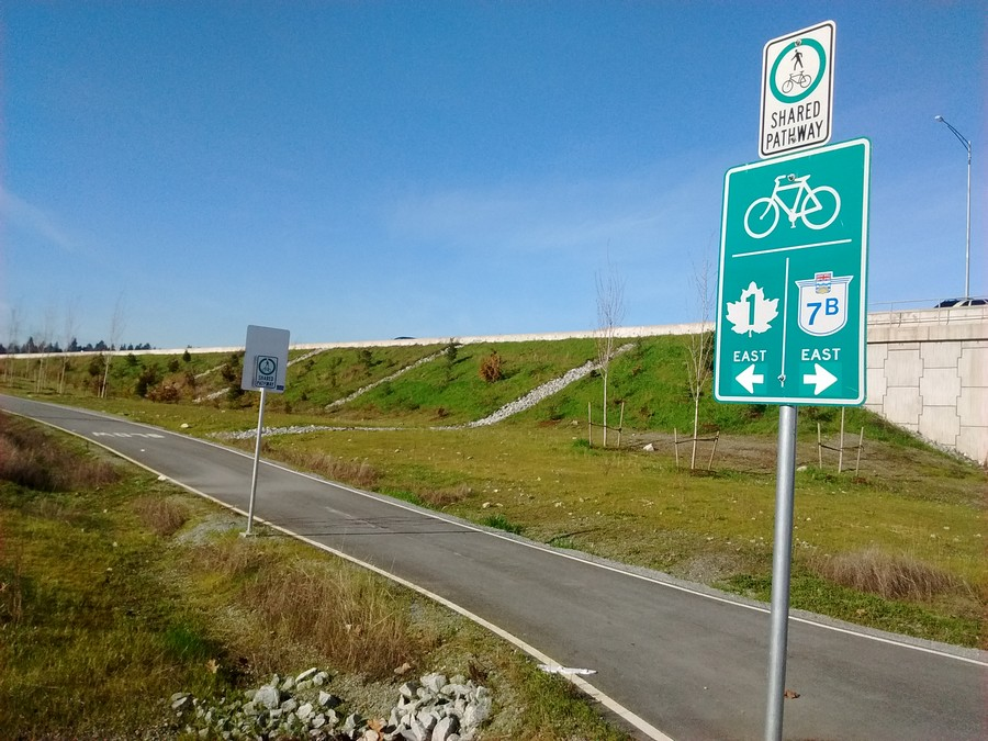 On the western, Coquitlam side, a signpost points the way to the Port Mann bridge cycle path alongise Highway 1 and over the Pitt River.