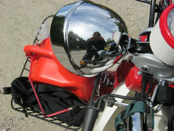 Ulrike's reflection in the chrome headlight of the Symba Honda Cub.