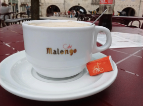 Cup and saucer of foamy coffee in French cafe, with a sugar cube with a bicycle logo