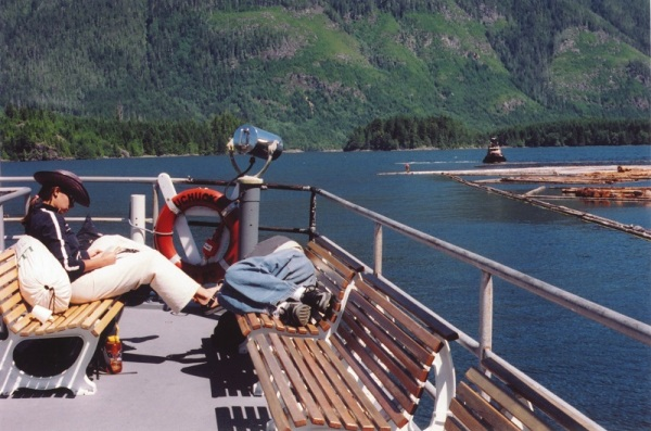 A woman reads a book aboard the vessel MV Uchuck with the BC coastline in the background, Canada.