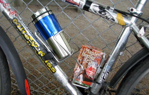 Close-up view of Ulrike's bicycle with a coffee mug in one water bottle holder, and a box of maple herbal team in the other.