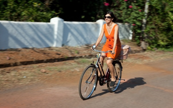 Ulrike in a sundress on her Indian bicycle on a quiet street in Goa, India.