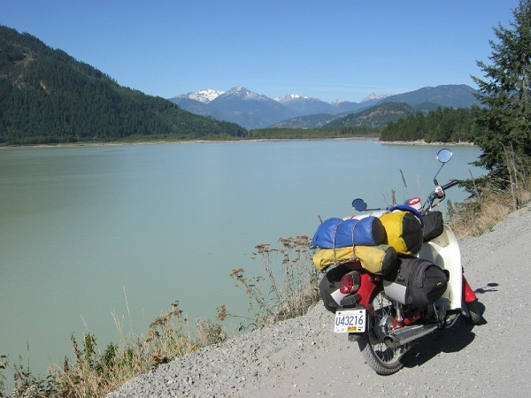 A 100cc Symba Honda Cub loaded with bags next to a scenic lake near Mount Currie, BC, Canada.