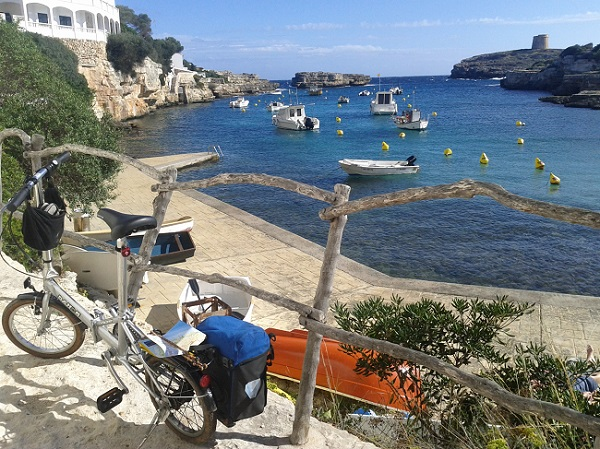 A Dahon folding bicycle overlooking a beautiful bay in Menorca, Spain.