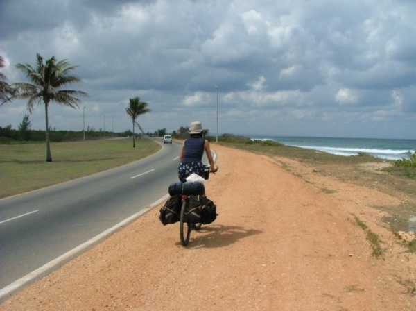Ulrike rides a touring bicycle on the red soil shoulder of a wide, untrafficked road into Matanzas, Cuba.