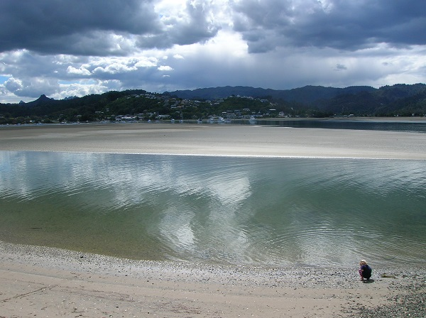 A boy plays on the shore of a wide river in Pauonui, New Zealand.