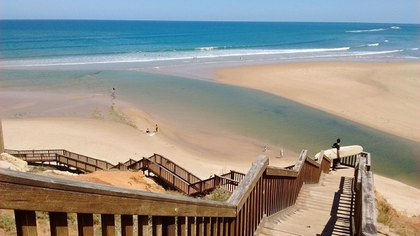 A long winding wooden staircase down a slope with a surf beach in the distance in South Australia.
