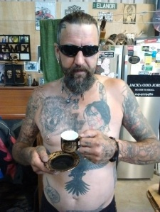 Brett all in tattoos holds a fine china cup and saucer in Australia.