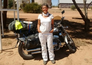 Ulrike dressed all in white standing in front of the loaded Honda Rebel motorcycle in Australia.