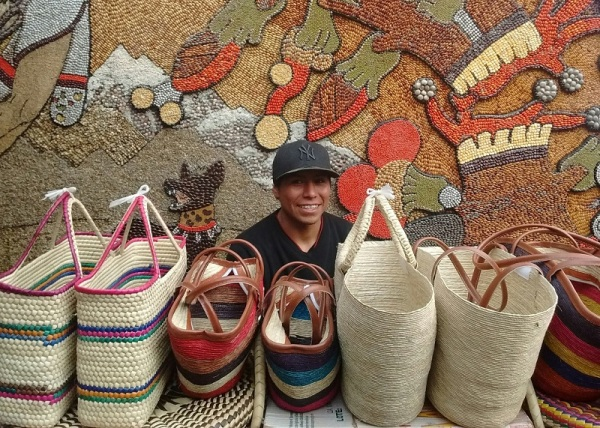 A row of hand-woven baskets, with a smiling seller, and a mosaic art wall behind him, made of maize and legumes in Tepoztlán, south of Mexico City. Photo: Ulrike Rodrigues
