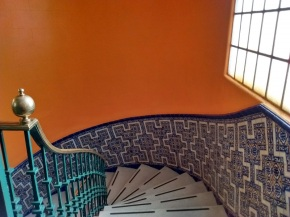 Top landing of a winding stairway with a window and ornate tiles in the Hotel Majestic, Mexico City. Photo: Ulrike Rodrigues
