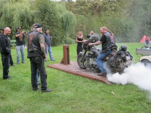 Motorbikers gather around a rider burning rubber on his rear tire on a wooden platform in BC, Canada.