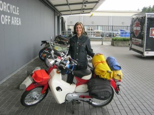 Ulrike stands behind the Symba Honda Cub loaded with camping gear.